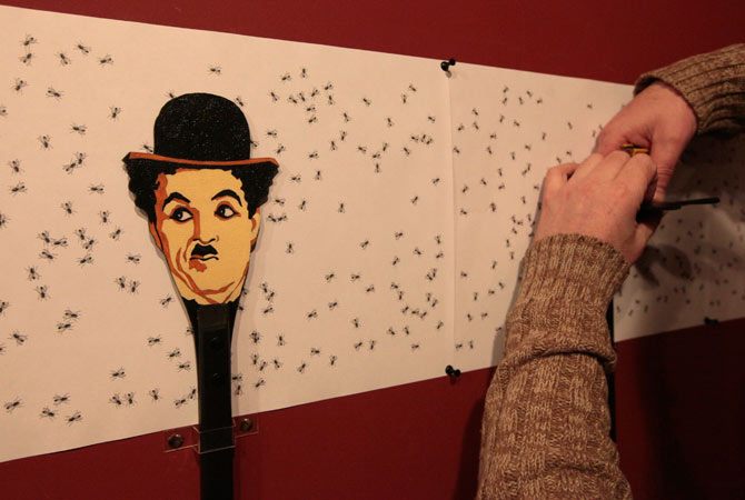 Russian artist Vasily Slonov works on an art installation, during the preparations for his exhibition at the Krasnoyarsk Museum Centre, with a flyswatter displaying an image of Charlie Chaplin seen in the foreground, in Russia's Siberian city of Krasnoyarsk.
