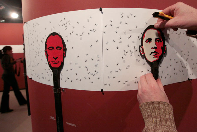 Russian artist Vasily Slonov works on an art installation, during the preparations for his exhibition at the Krasnoyarsk Museum Centre, with flyswatters displaying an image of Russia's President Vladimir Putin (L) and US President Barack Obama seen in the foreground, in Russia's Siberian city of Krasnoyarsk.