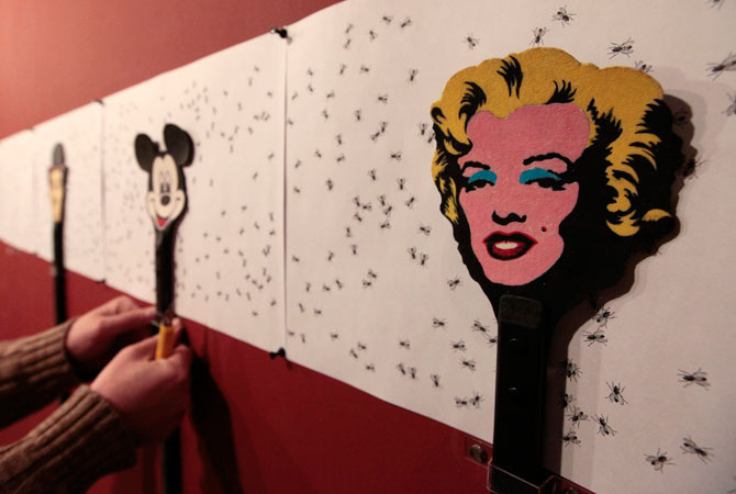 Russian artist Vasily Slonov works on an art installation, during the preparations for his exhibition at the Krasnoyarsk Museum Centre, with a flyswatter displaying an image of Marilyn Monroe seen in the foreground, in Russia's Siberian city of Krasnoyarsk.