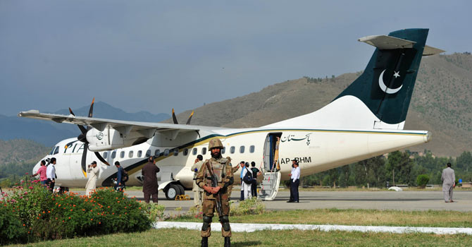 A Pakistani army soldier stands guard in front of the Pakistan International Airline (PIA) after it flew a test flight to Saidu Sharif in Swat Valley on October 10, 2012. The PIA have planed to reopen its flights for Swat valley after it was shut down in 2007 due to security situation.  – Photo by AFP
