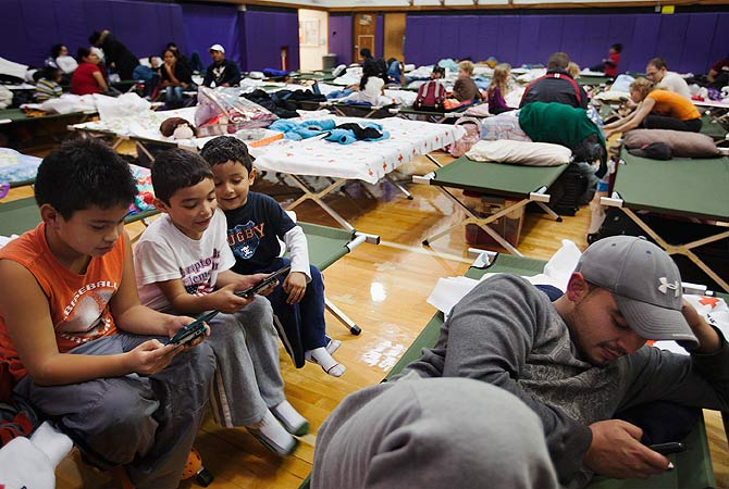 Young boys play video games while in the sleeping area of a Red Cross shelter in Hampton Bays, New York.-Photo by Reuters