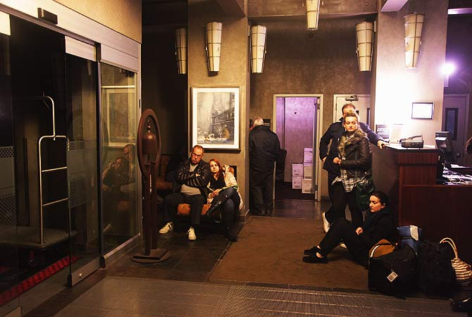 People wait in the lobby of the Hampton Inn Manhattan-SoHo after the power went out in New York City.-Photo by AP