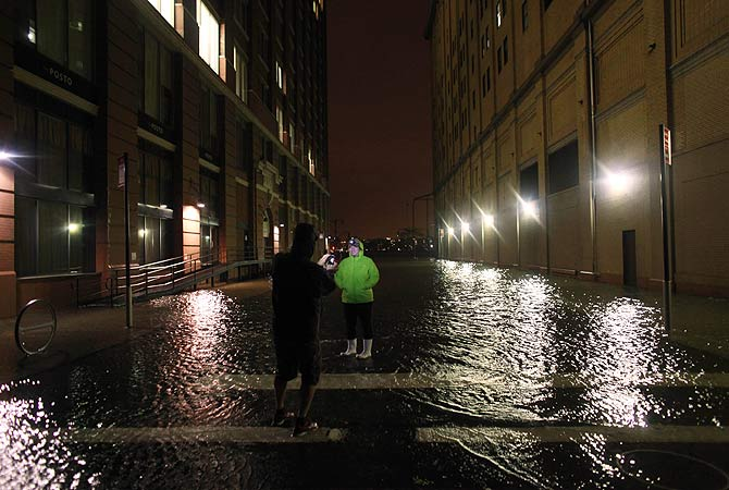 People take photographs in flood water in the Meatpacking District in Manhattan, New York.-Photo by AFP