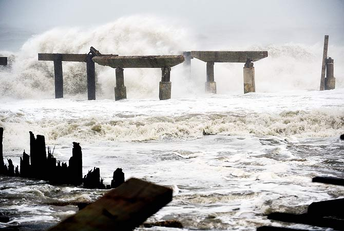 Waves crash against a previously damaged pier before landfall.-Photo by AFP