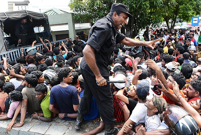 Sri Lankan police speak to cricket fans waiting to buy tickets. -Photo by AFP