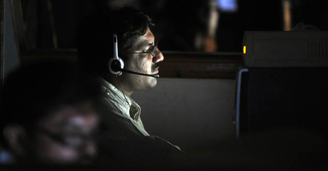 A Pakistani stockbroker watches the share price monitor during a trading session at the Karachi Stock Exchange (KSE) – File photo by AFP