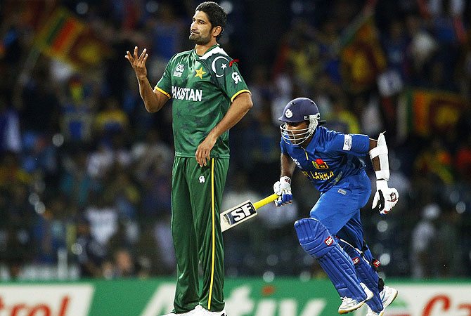 Sohail Tanvir, left, gestures to his teammate after Sri Lanka's captain Mahela Jayawardene, right, hit a boundary on his delivery. -Photo by AP