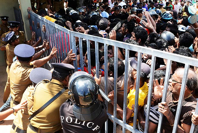 Sri Lankan police hold a gate as cricket fans wait to buy tickets for the semi-final between Sri Lanka and Pakistan. -Photo by AFP