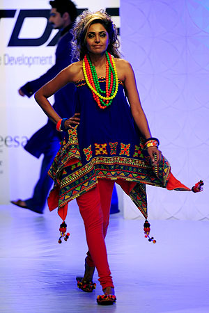 Eraj Manzoor presents a creation by designer Rung Ja during a fashion show in Karachi.-Photo by AFP