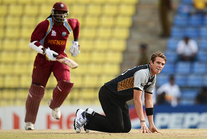 Tim Southee looks on as West Indies' Chris Gayle (L) takes a run. -Photo by Reuters