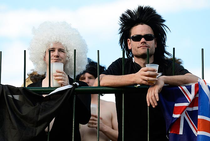 New Zealand cricket fans wearing wigs look on during the match. -Photo by Reuters
