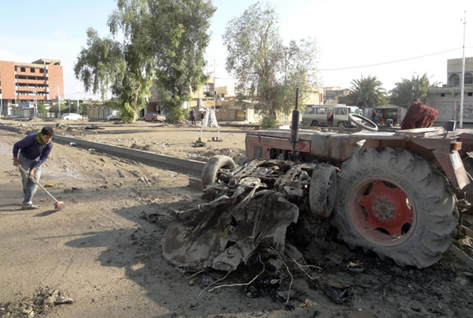 An Iraqi sweeps the debris following one of two car bombs in the northern Iraqi city of Kirkuk, on November 14, 2012.