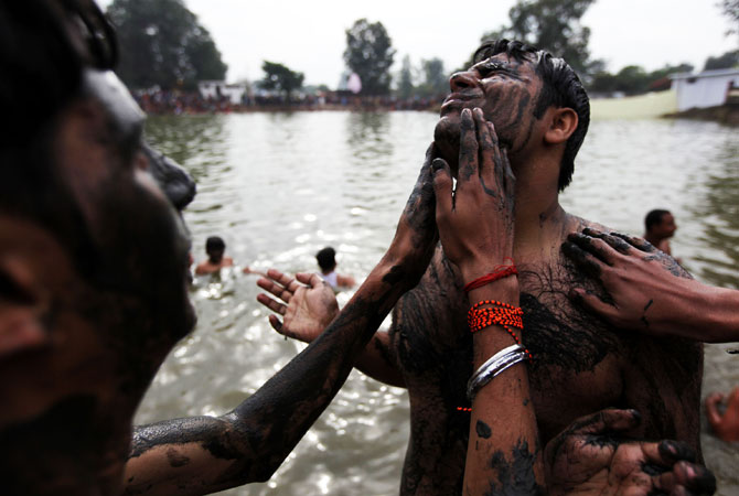 Indian Hindu devotees smear themselves with mud before taking a holy dip during the annual farmers fair at Shama Chak Jhiri,  some 22kms from Jammu on November 28, 2012. ? Photo by AFP