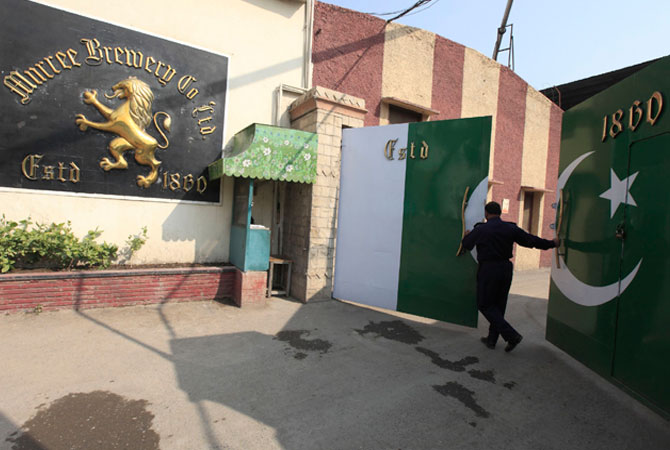 A guard at Pakistan's lone beer maker, Murree Brewery, closes the main gate at the factory in Rawalpindi.