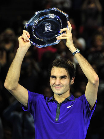 Federer poses with the runners-up shield after being beaten by Serbia's Novak Djokovic in the singles final against on the eighth day of the ATP World Tour Finals tennis tournament in London.