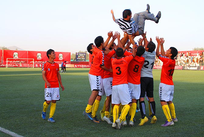 The Mazar e Sharif team celebrates with their coach.