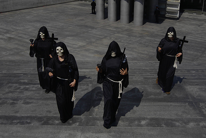 People in skull masks walk near an altar assembled in homage of people who died of diabetes and obesity, during a demonstration in front of the Mexican Ministry of Health in Mexico City. The walk was part of the Day of the Dead.
