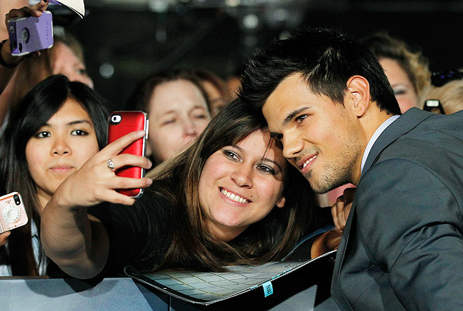 "Cast member Taylor Lautner poses with a fan at the premiere of ""The Twilight Saga: Breaking Dawn - Part 2"" ? Reuters Photo"