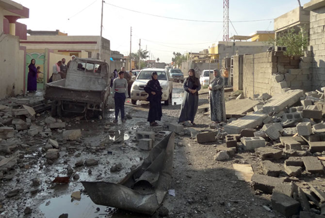 Iraqis looks at the damage to buildings following one of  two car bombs in the northern Iraqi city of Kirkuk.