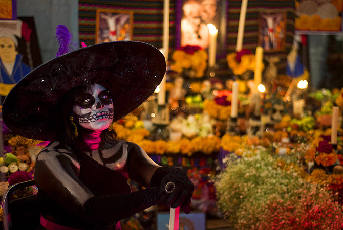 A woman in dressed up as the death poses with an Altar for the Dead in the background in Mexico city, during preparations on the eve of the Day of the Dead celebrations.
