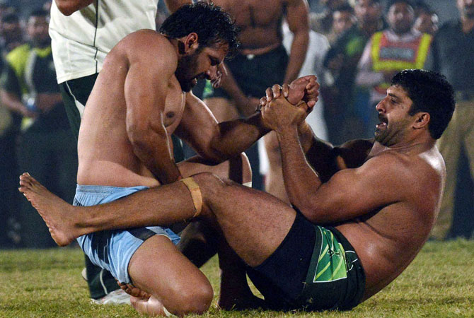 A Pakistani kabbadi player (Right) is tackled by his Indian opponent during the Kabaddi Asia Cup final match.
