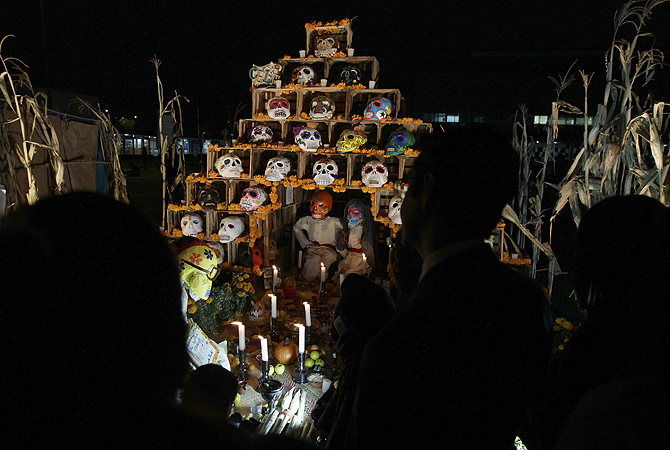 Visitors look at an art installation of skulls at an altar assembled by artists for Day of the Dead celebrations at the National Autonoma University of Mexico in Mexico City.