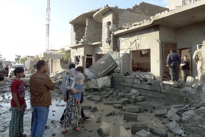 An Iraqi family looks at the damage to a building following one of  two car bombs in the northern Iraqi city of Kirkuk.