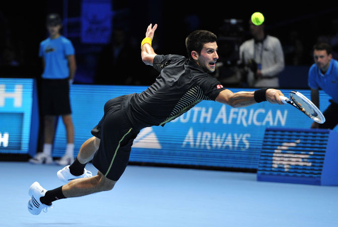 Djokovic dives for a return against Switzerland's Roger Federer during the singles final on the eighth day of the ATP World Tour Finals tennis tournament in London.