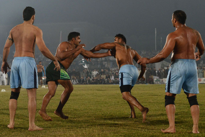 A Pakistani kabbadi player (2nd Left) attempts to tag his Indian opponents during the Kabaddi Asia Cup final match.