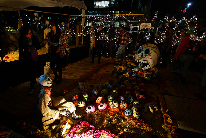 Visitors look on at an art installation of a skeleton and skulls at an altar assembled by artists for the Day of the Dead celebrations at the National Autonoma University of Mexico pictures in Mexico City.
