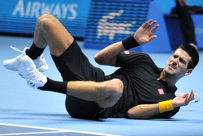 Djokovic hits the ground after diving for a return.