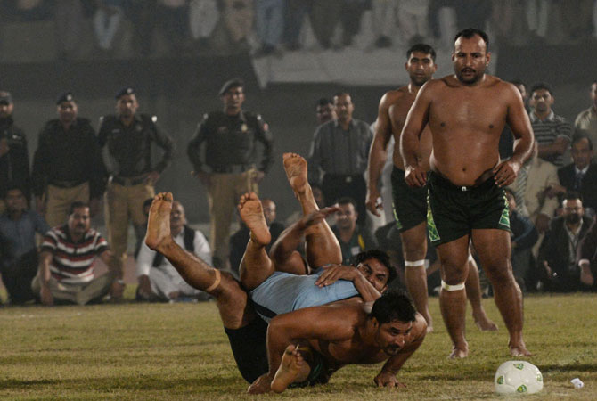A Pakistani kabbadi player (Centre) is tackled by his Indian opponent during the Kabaddi Asia Cup final match in Lahore late on November 5, 2012.