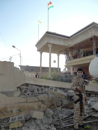 An Iraqi soldier stands infront of a collapsed wall following one of two car bombs in the northern Iraqi city of Kirkuk on November 14, 2012.