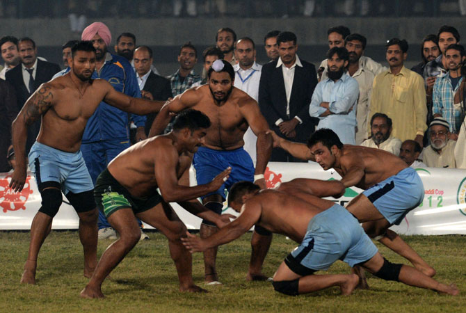 A Pakistani kabbadi player (2nd Left) attempts to tag his Indian opponents during the Kabaddi Asia Cup final match in Lahore late on November 5, 2012.