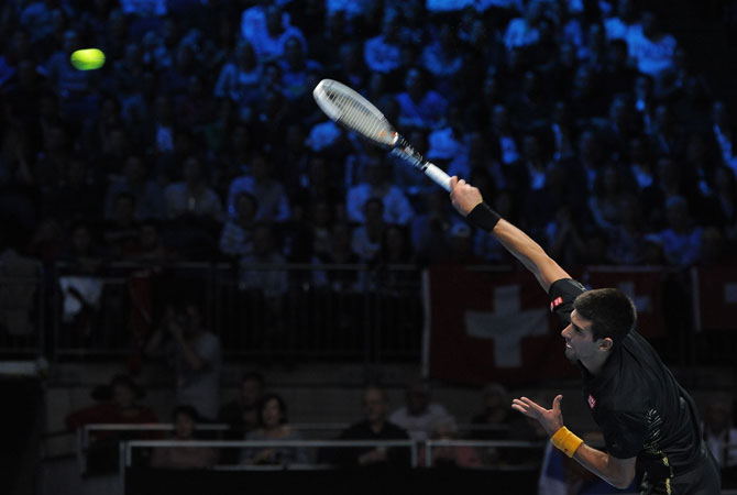 Djokovic serves against Switzerland's Roger Federer during the singles final on the eighth day of the ATP World Tour Finals tennis.
