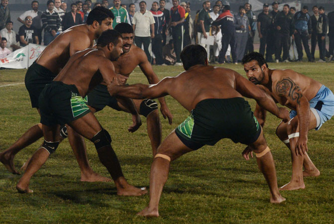 An Indian kabbadi player (Right) attemps to tag Pakistani opponents during the Kabaddi Asia Cup final match in Lahore late on November 5, 2012.