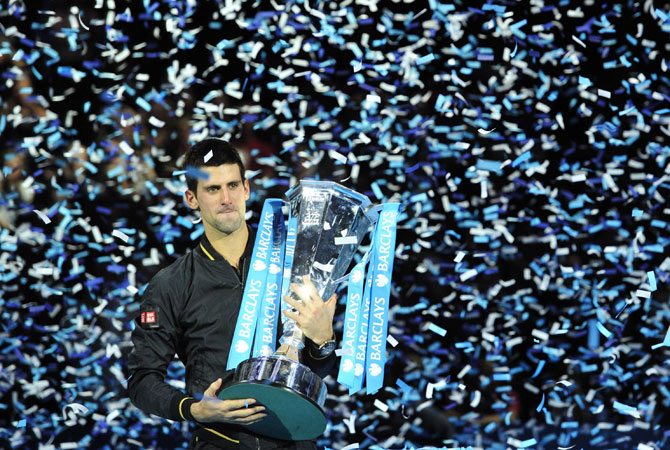 Djokovic poses with the winners' trophy after the singles final against Switzerland's Roger Federer on the eighth day of the ATP World Tour Finals tennis tournament.