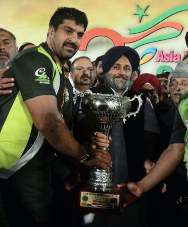 Pakistani kabbadi team captain Musharraf Javed (Left) receives the trophy from Indian Punjab state Deputy Chief Cinister Sukhbir Singh Badal after the final of the Kabaddi Asia Cup in Lahore late on November 5, 2012.