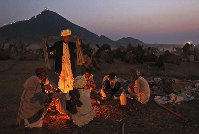 Indian camel herders sit around a fire at the annual Pushkar Fair in Pushkar, Rajasthan, India.?Photo by AP