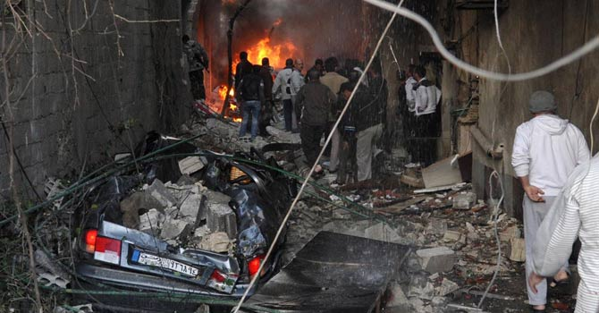 A handout picture released by the Syrian Arab News Agency (SANA) on November 28, 2012, shows Syrian men inspecting the scene of a car bomb explosion in Jaramana, a mainly Christian and Druze suburb of Damascus. -AFP Photo