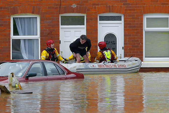 Firefighters in a boat rescue a stranded man from a house on a flooded street in St Asaph, north Wales.?Photo by Reuters