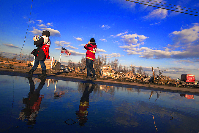 Red Cross volunteers walk past the remaining foundations of homes destroyed by the storm surge of superstorm Sandy in the Staten Island borough neighborhood of Oakwood in New York.?Photo by Reuters
