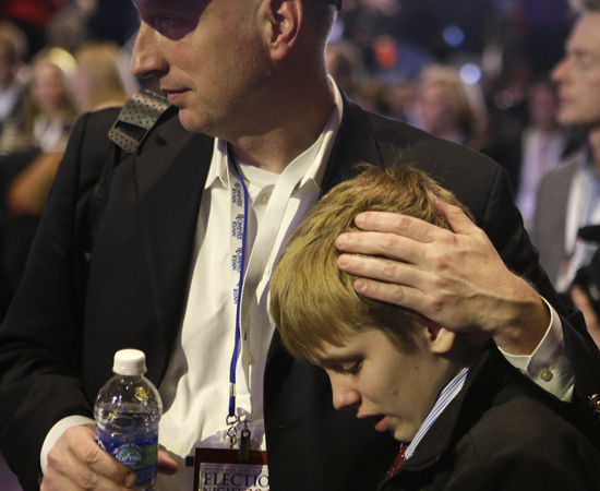 David French, of Columbia, Tenn., consoles his son Austin as they watch vote results displayed on a screen during the election night rally for Republican presidential candidate and former Massachusetts Gov. Mitt Romney, Tuesday, Nov. 6, 2012, in Boston.—Photo by AP