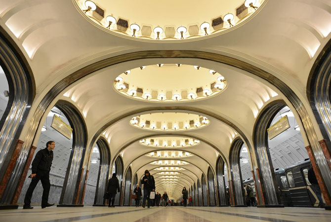Subway passengers walk at the Mayakovskaya metro station in Moscow.