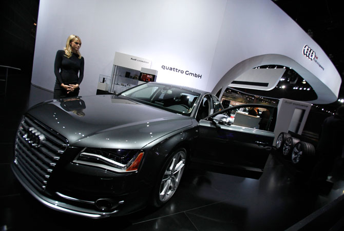 A hostess stands next to a 2013 Audi S8 at the 2012 Los Angeles Auto Show in Los Angeles, California November 28, 2012.