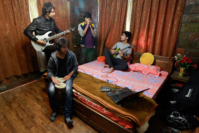 Members of the band ?Sign - the signature of music? (L-R) guitarist Zahoor Qadir, 18, drummer Muneeb Khan, 17, guitarist and lead singer Qassam Dar, 18, and guitarist Azan Mullick, 18, record a song at Azan's home in Srinagar.