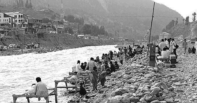 Visitors resting on charpoys (portable bed) on the bank of Swat River.–Photo by Dawn