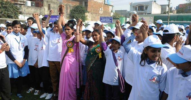 Indian campaigners Priyanka Bharti (L) along with Priyanka Kumari (R) hold hands with school children as they take part in a function to mark World Toilet Day in New Delhi.Sulabh International, a non-proft group, organised the function to reward two Indian brides who had protested against their husband's families because there was no toilet in their matrimonial household. – Photo by AFP