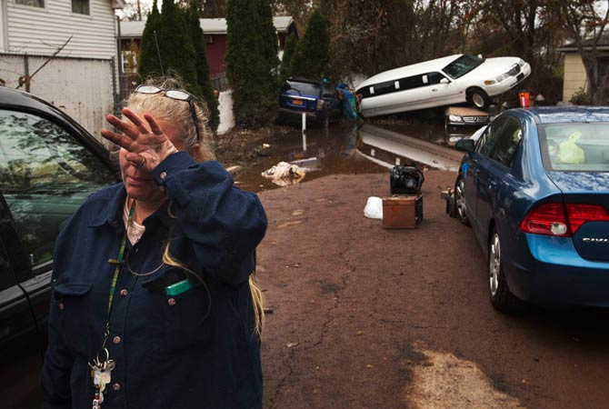 A woman weeps after learning that a neighbor presumed missing is okay while cleaning out her home in a neighborhood heavily damaged by Hurricane Sandy in the New Dorp Beach neighborhood of the Staten Island borough of New York, November 1, 2012.