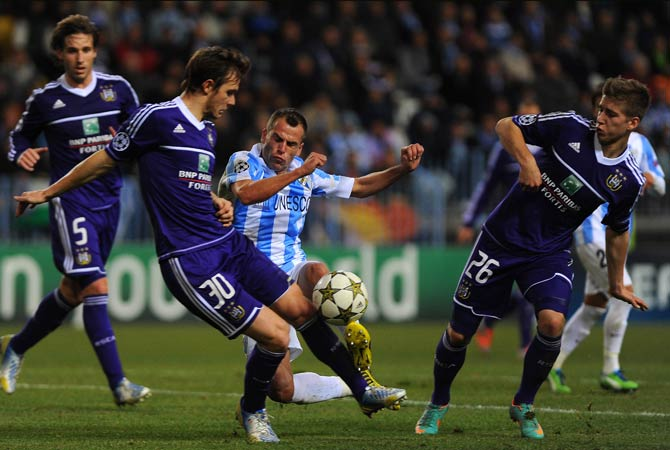 Malaga's Portuguese midfielder Duda vies with Anderlecht's Belgian midfielder Guillaume Gillet (Left) and Belgian midfielder Dennis Praet (Right) during the UEFA Champions League Group C football match Malaga CF vs RSC Anderlecht at La Rosaleda stadium in Malaga.